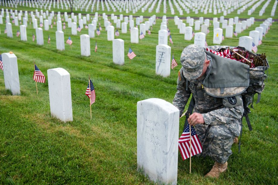 A U.S. Army 3d U.S. Infantry Regiment (The Old Guard) Soldier places American flags at headstones in Section 64 of Arlington National Cemetery during Flags In, May 21, 2015, in Arlington, Va. The Old Guard has held this honor and privilege of conducting Flags In since 1948.